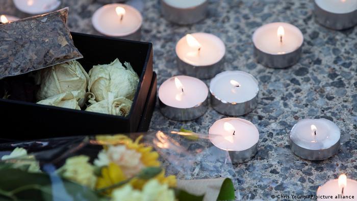 Foto simbólica de candelas y flores en señal de luto.