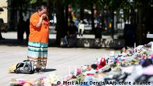 VANCOUVER, CANADA - MAY 29 : A woman mourns over 215 pairs of kids shoes outside Vancouver Art Gallery during a memorial on May 29, 2021 in Vancouver, British Columbia, Canada The remains of 215 children have been found buried at a Canadian residential school, an Indigenous band confirmed Thursday. Mert Alper Dervis / Anadolu Agency