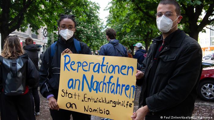 Reparaciones para los descendientes en lugar de ayuda al desarollo, dice el letrero exhibido durante una protesta en Berlín.