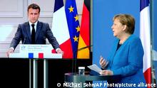 French President Emmanuel Macron is seen on a video screen during a joint press conference with German Chancellor Angela Merkel, right, as part of a virtual Plenary Session of the Franco-German Council of Ministers in Berlin, Germany, Monday, May 31, 2021. (AP Photo/Michael Sohn, pool)