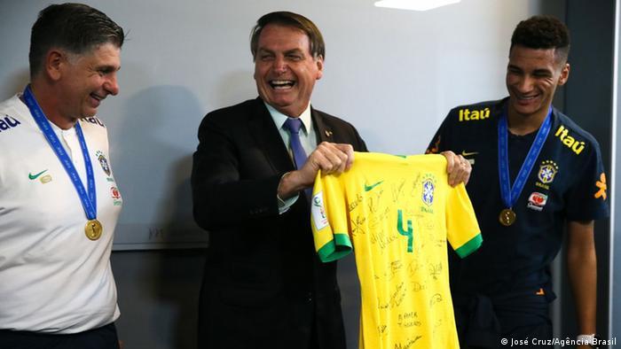 Brazilian president Jair Bolsonaro grinning while holding national soccer strip