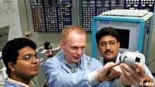 Berlin: Martin Reets, Mitarbeiter der Firma SENTECH Instruments GmbH, erklärt am 14.06.2004 in Berlin den indischen Kunden Pankaj Chaudhary (r.) und Aji Baby (l) Teile einer neuen Plasma-Ätzanlage. Die Anlage dient zur Fertigung mikrooptischer und mikroelektronischer Bauelemente und erreicht die dreifache Produktivität ihres Vorgängertyps. Herzstück der für die industrielle Kleinserienfertigung sowie für Forschungseinrichtungen entwickelten Anlage ist ein Ätz-Reaktor, in dem Strukturen auf Galliumarsenid-Wafern (Halbleiter-Scheiben) und optischen Materialien wie Glas und Quarz mit Hilfe von Ä