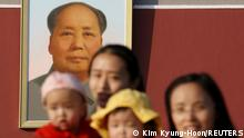 FILE PHOTO: Two women and their babies pose for photographs in front of the giant portrait of late Chinese chairman Mao Zedong on the Tiananmen Gate in Beijing November 2, 2015. REUTERS/Kim Kyung-Hoon/File Photo