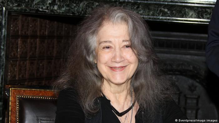 Martha Argerich with long gray hair smiles