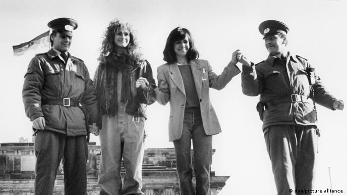 Sally Field and Julia Roberts standing on the Berlin Wall with two GDR border guards at Brandenburg Gate in 1990