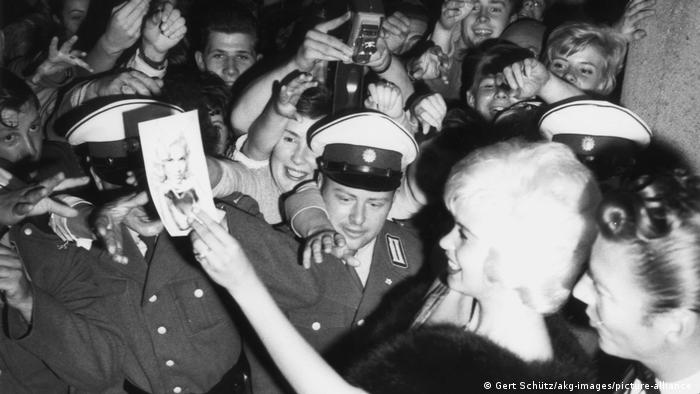 Jayne Mansfield holding a photo of herself, surrounded by police officers and smiling fans.