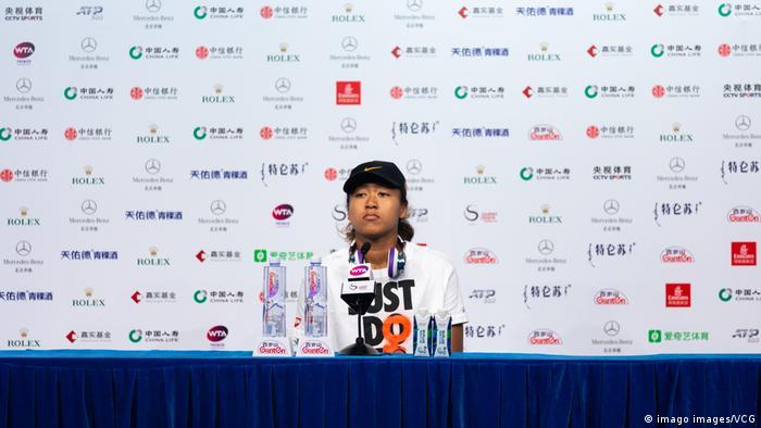 Naomi Osaka sits alone at a press conference in China
