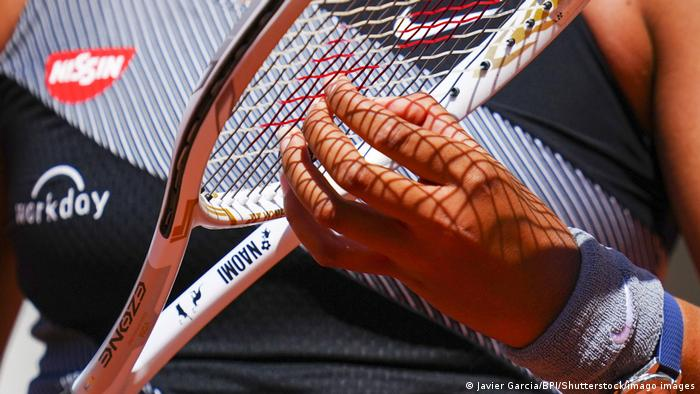 Naomi Osaka plucks her racket at the 2021 French Open