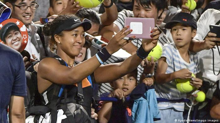 Naomi Osaka pauses for photos with fans in Osaka, Japan
