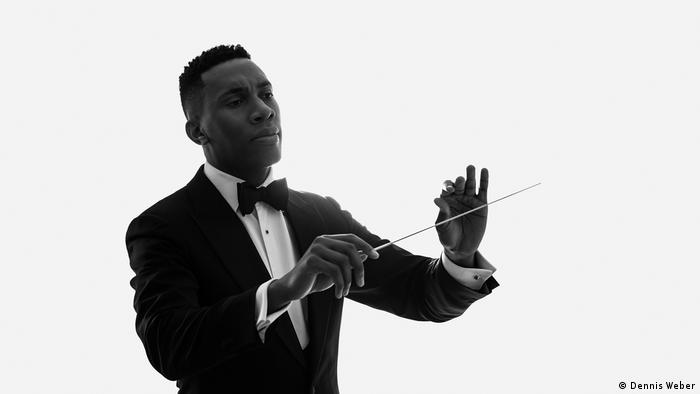 a man holding a conductor's wand