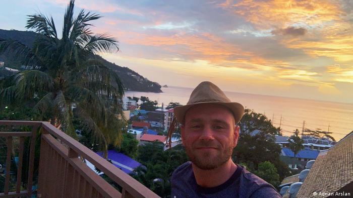 Adnan Arslan steht auf einem Balkon, hinter ihm ein Sonnenuntergang mit Wasser. Bügerrat Klima 2021 | Adnan Arslan