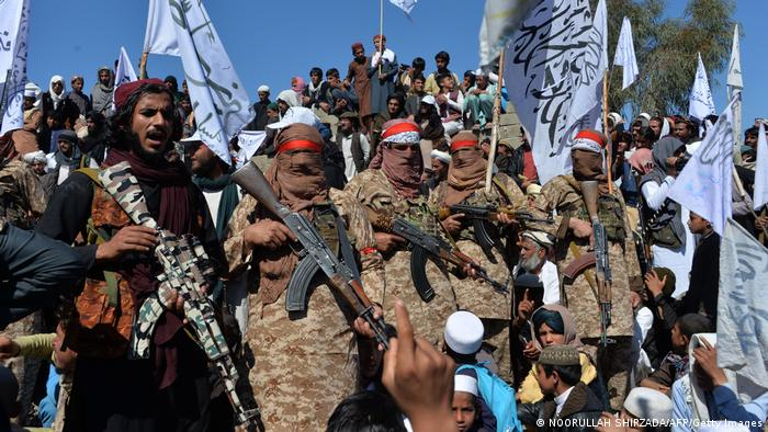 Blick auf eine größere Gruppe bewaffneter Männer im Zentrum des Bildes, teils mit Tüchern vor dem Gesicht. Sie stehen am Rand eines Hügels, einige tragen Fahnen. Unterhalb und oberhalb der Kämpfer sind zahlreiche Zivilisten zu sehen, darunter auch Kinder