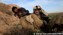 FILE PHOTO: U.S. Marine Lance Corporal Chris Sanderson, from Flemington, New Jersey shouts as he tries to protect an Afghan man and his child after Taliban fighters opened fire in the town of Marjah, in Nad Ali district, Helmand province, Afghanistan, February 13, 2010. REUTERS/Goran Tomasevic/File Photo