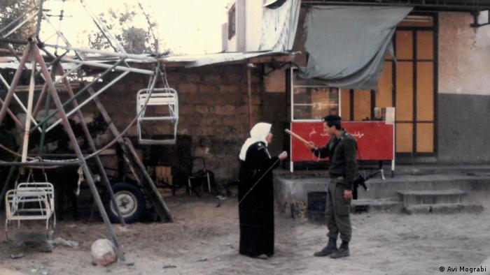 Film still 'The First 54 Years – An Abbreviated Manual for Military Occupation': soldier pointing a stick towards veiled woman, rudimentary fun fair swing in the background.