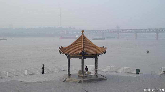 Still from film 'A River Runs, Turns, Erases, Replaces': a foggy view of the Yangtze River and its riverside promenade.