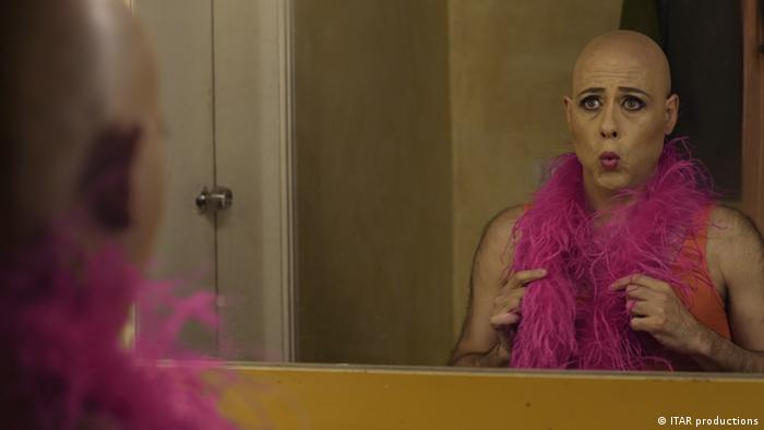 Film still 'Miguel's War': a bald person wearing nothing but a pink boa, pouting lips while staring in a mirror.