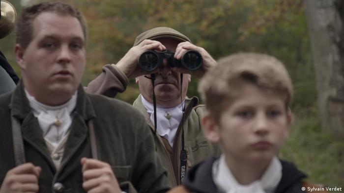 Film still 'We': a man looking though binoculars, two boys in the foreground.
