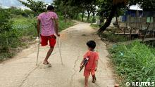 """*** Dieses Bild ist fertig zugeschnitten als Social Media Snack (für Facebook, Twitter, Instagram) im Tableau zu finden: Fach """"Images"""" —> Myanmar *** Ko Phyo, 24, a protester who lost one leg during an anti-coup protest, walks on a street with his two-year-old son Paing Phyo Oo as they head to his home on the outskirts of Yangon, Myanmar, May 22, 2021. I feel terrible when he asked, 'Dad, where's your leg?', Ko Phyo said. So, I replied, 'A dog's eaten my leg but it will grow later.' And he still believes it. REUTERS/Stringer SEARCH PHYO YANGON FOR THIS STORY. SEARCH WIDER IMAGE FOR ALL STORIES Ganze Story: https://reut.rs/3c84RLq"""