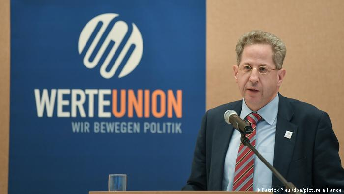 Hans-Georg Massen speaking into a microphone standing in front of a sign reading Werteunion - we move politics