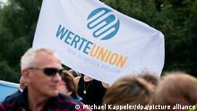 13/08/2019 Eine Anhängerin der Werteunion, eines konservativen Kreises von Mitgliedern der Unionsparteien, steht mit einer Fahne bei einer Gedenkveranstaltung und Kranzniederlegung an der Glienicker Brücke zum Gedenken an den Bau der Berliner Mauer vor 58 Jahren.