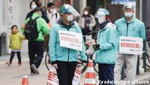 Officials wearing face masks ask pedestrians not to gather to watch a half-marathon race being held amid the coronavirus pandemic at the venue of the Tokyo Olympics marathon as a test event in the northern Japan city of Sapporo on May 5, 2021. (Kyodo)