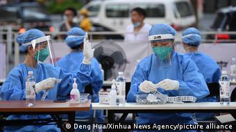 Обработка анализов на коронавирус в одном из центров тестирования в Гуанчжоу