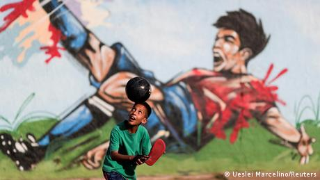 BdTD | A child plays soccer in a street at the neighborhood of Ceilandia in Brasilia