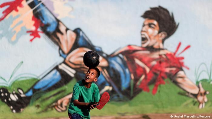 Ovaj dečak će se sigurno obradovati što za desetak dana u Braziliji, gde živi, počinje Kopa Amerika. Osim glavnog grada Brazila, igraće se još na Marakani u Riju, u Kujabi i Gojaniji. Fudbalsko prvenstvo Južne Amerike - i to u Brazilu - nailazi na kritike. Jer, u toj zemlji se i dalje beleži oko 80.000 zaraza dnevno, a do sada se sa koronom povezuje gotovo pola miliona smrti.