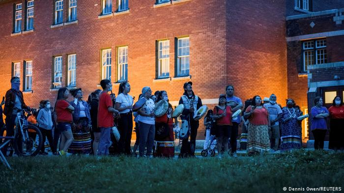 Kamloops residents and First Nations people gather to listen to drummers and singers at a memorial for 215 children found near the school