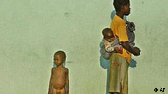 Hunger in Angola: Mutter mit Baby und Kind wartet vor einem Hospital in Kuito auf Nahrung