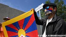 Activists hold the Tibetan flag underneath a street sign reading 'Dalai Lama street', close to a territory of the planned Chinese Fudan University campus, in 9th district, Ferencvaros of Budapest, Hungary on June 2, 2021. - Budapest has renamed streets around the planned site of a top Chinese university to protest an unwanted project forced on it by Prime Minister Viktor Orban's government, the city's mayor said. (Photo by Attila KISBENEDEK / AFP)