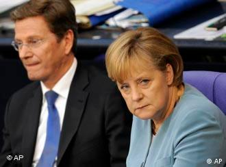 Chancellor Angela Merkel, looking grumpy, sat next to Foreign Minister Guido Westerwelle in parliament.
