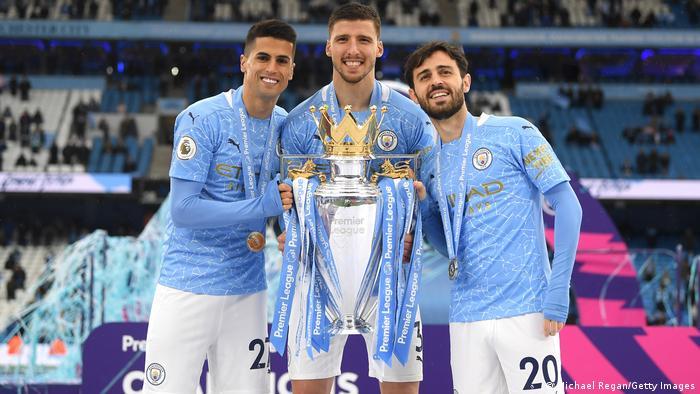 Joao Cancelo, Ruben Dias and Bernardo Silva celebrate with the Premier League Trophy
