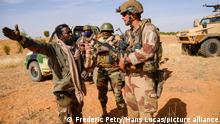 Barkhane, operation Eclipse. In the middle of the Sahelian desert, a joint patrol between the French soldiers of the Barkhane force and the soldiers of the Malian Armed Forces (FAMa) of the G5 Sahel. One Malian soldier talk to a French officer. Mali, Gourma (Tri-border region), January 2021. Photography by Frederic Petry / Hans Lucas. Barkhane, operation « Eclipse ». Au milieu du desert Sahelien, une patrouille conjointe entre les soldats francais de la force Barkhane et les soldats des Forces Armees Maliennes (FAMa) du G5 Sahel. Un soldat maliens s entretienne avec un officier francais. Mali, Gourma (region des trois frontieres), janvier 2021. Photographie de Frederic Petry / Hans Lucas.