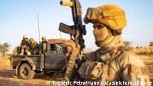 In the middle of the Sahel desert in northern Mali, a French soldier from the Barkhane force, armed and helmeted, stands protectively in front of a Malian army (FAMA: Forces Armées Maliennes) military pick-up. Malian soldiers sit at the back of the pick-up. They are helmeted and armed. All of them are participating in a military operation against armed terrorist groups (GAT) with the French Barkhane forces. Mali, Gourma (Tri-border region), January 2021. Photography by Frederic Petry / Hans Lucas. Au milieu du desert du sahel, au Nord Mali, un militaire francais de la force Barkhane, arme et casque, se tient debout, en protection, devant un pick-up militaire de l armee malienne (FAMA Forces Armees Maliennes). Des soldats maliens sont assis a l arriere du pick-up. Ils sont casques et en armes. Tous participent a une operation militaire contre les groupes armes terroristes (GAT) avec les forces francaises de Barkhane. Mali, Gourma (region des trois frontieres), janvier 2021. Photographie de Frederic Petry / Hans Lucas.