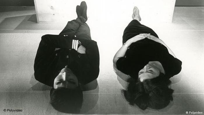 Film still, man and women lying on their backs on the ground (Polyvideo)