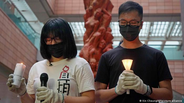 Hong Kong Alliance in Support of Patriotic Democratic Movements of China Vice Chairperson Chow Hang-tung, left, stands in front of the Pillar of Shame statue