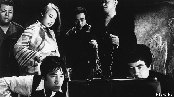 Verschiedene Männer und eine Frau schauen auf ein Fernsehgerät - Szene aus Die Nacht des Mörders (Foto: polyfilm video)