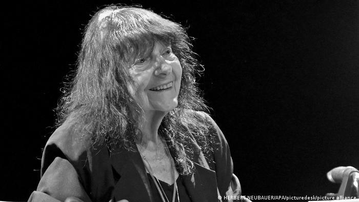 Autorin Friederike Mayröcker, das Haar offen, trägt ein schwarzes Kleid und mehrere lange Ketten. Sie lacht. Das Foto ist schwarz/weiß.