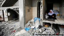 A Palestinian woman cooks amid the rubble of her house, which was destroyed by Israeli air strikes during the Israeli-Palestinian fighting, in Gaza May 23, 2021. Picture taken May 23, 2021. REUTERS/Mohammed Salem