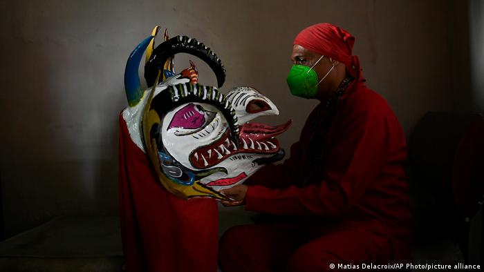 A man wearing a medical mask holds his papier-mache mask in front of him