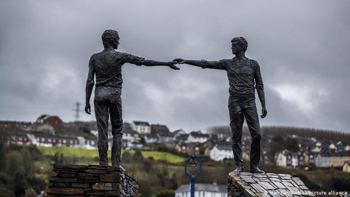 Skulptur Hands Across the Divide in der Grenzstadt Derry, zwei Männer reichen einander die Hand über die Grenze.