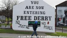 14.03.2019, Großbritannien, Londonderry: Ein junger Mann geht an einer Graffiti beschmierten Hauswand vorbei an der You are now Entering Free Derry steht. Ein britischer Ex-Soldat, der am «Blutsonntag» 1972 in der nordirischen Stadt Londonderry beteiligt war, muss sich wegen zweifachen Mordes vor Gericht verantworten. Foto: Liam Mcburney/PA Wire/dpa +++ dpa-Bildfunk +++
