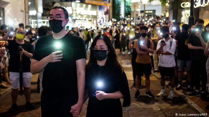 People hold up their phones with the light