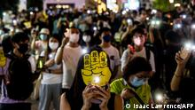 People hold up their phones with the light on in the Causeway Bay district of Hong Kong on June 4, 2021, after police closed the venue where Hong Kong people traditionally gather annually to mourn the victims of China's Tiananmen Square crackdown in 1989 which the authorities have banned citing the coronavirus pandemic and vowed to stamp out any protests on the anniversary. (Photo by ISAAC LAWRENCE / AFP)