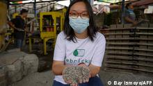This photograph taken on April 7, 2021 shows Rebrick founder Novita Tan holding chopped plastic waste, used to form bricks that use the material mixed with cement and sand, at a brick-making factory in Jakarta. - Alarmed by the mountains of plastic waste leaching into Indonesia's waters, two best friends are taking on the environmental menace by turning crisp bags and shampoo packets into paving bricks. (Photo by BAY ISMOYO / AFP) / TO GO WITH AFP STORY INDONESIA-WASTE-ENVIRONMENT,FOCUS BY AGNES ANYA