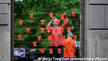 June 5, 2021, Ottawa, on, Canada: Orange fabric cut in the shape of shirts are pinned to string during a vigil held by Ottawa faith communities, to honour the 215 children whose remains were found at the grounds of the former Kamloops Indian Residential School at Tk'emlups te Secwépemc First Nation in Kamloops, B.C., at the Human Right's Monument in Ottawa, on Saturday, June 5, 2021. (Credit Image: © Justin Tang/The Canadian Press via ZUMA Press