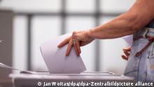 Eine Frau wirft ihren Stimmzettel in eine Urne in einem Wahllokal. Die Wahl zum neuen Landtag in Sachsen-Anhalt ist die letzte Landtagswahl vor der Bundestagswahl im September 2021.