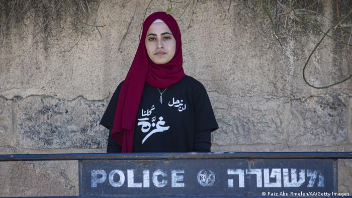 Palestinian activist Muna al-Kurd poses in the Sheikh Jarrah neighborhood behind a police barrier
