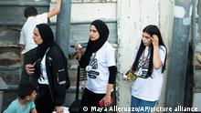 Palestinian activist Muna el-Kurd, center, wears a medal from a marathon as she leaves the site where Israeli police fired tear gas during clashes in the Silwan neighborhood of east Jerusalem, Friday, June 4, 2021. The Palestinian Red Crescent says 23 runners were injured when police fired tear gas and stun grenades at an activist-organized marathon in solidarity with Palestinians in east Jerusalem threatened with evictions. (AP Photo/Maya Alleruzzo)